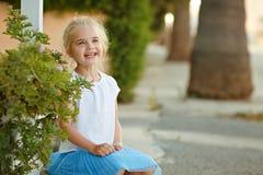 Bionda della ragazza 5 anni che ridono sui precedenti degli alberi nel summe Fotografie Stock