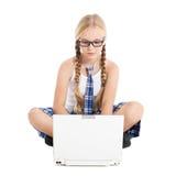 Scolara che porta un uniforme scolastico che si siede sul pavimento con un computer portatile sul vostro rivestimento Immagini Stock