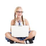 Scolara che porta un uniforme scolastico che si siede sul pavimento con un computer portatile sul vostro rivestimento Immagini Stock Libere da Diritti
