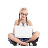 Scolara che porta un uniforme scolastico che si siede sul pavimento con un computer portatile sul vostro rivestimento Fotografie Stock