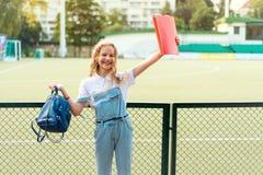 Bionda della scolara con gli occhi azzurri che tengono una cartella rossa e uno zaino fotografie stock
