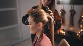 Bionda di modello caucasica dell'acconciatura del truccatore del parrucchiere Disperde la vernice e rende i capelli ordinati Usa  archivi video