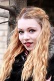 Bionda emozionale con capelli lunghi che sorride alla macchina fotografica, porto del primo piano Fotografia Stock