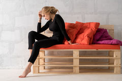 Bionda esile su un sofà di legno in una posa malinconica