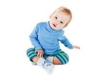 Bionda felice sveglia del bambino in un maglione blu che gioca e che sorride sul bianco Fotografie Stock Libere da Diritti