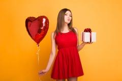 Bionda felice in vestito rosso che tiene un pallone e un contenitore di regalo fotografia stock libera da diritti