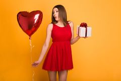Bionda felice in vestito rosso che tiene un pallone e un contenitore di regalo fotografie stock libere da diritti