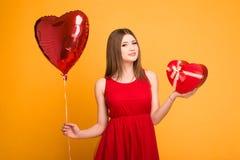 Bionda felice in vestito rosso che tiene un pallone e un contenitore di regalo fotografia stock