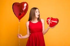 Bionda felice in vestito rosso che tiene un pallone e un contenitore di regalo immagini stock libere da diritti