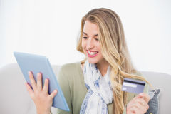 Bionda graziosa allegra che usando la sua carta di credito per comprare online Fotografia Stock