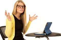 Bionda graziosa con l'espressione frustrata che si siede allo scrittorio con il IP Fotografie Stock