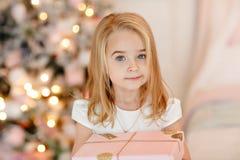 Bionda molto sveglia della bambina in un vestito bianco che tiene un contenitore di regalo fotografia stock libera da diritti
