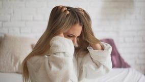 Bionda nervosa con la forfora sulla sua testa, graffiante la sua pelle Irritazione, itching della testa video d archivio