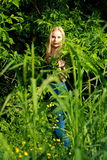 Bionda sorridente nella foresta Fotografia Stock