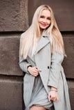 Bionda splendida che posa alla via in cappotto grigio immagini stock