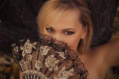 Bionda splendida con il fan di carnevale Immagine Stock
