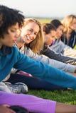 Bionda sportiva sorridente che allunga durante la classe di forma fisica Fotografia Stock