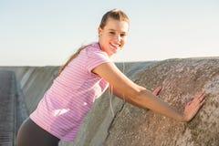 Bionda sportiva sorridente che allunga e che ascolta la musica Fotografia Stock Libera da Diritti