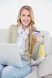 Bionda sveglia felice che usando la sua carta di credito per comprare online Fotografia Stock Libera da Diritti