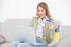 Bionda sveglia sorpresa che usando la sua carta di credito per comprare online Fotografia Stock