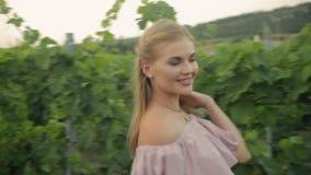 Bionda tenera nel vestito rosa che cammina lungo la vigna verde stock footage