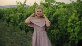 Bionda tenera nel vestito rosa che cammina lungo la vigna verde archivi video