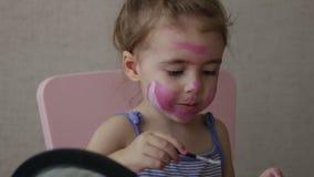 Bionda tre bande di colore della pittura del bambino di anni sul suo fronte che esamina specchio stock footage