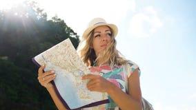 Bionda turistica della ragazza in cappello e con lo zaino che esamina la mappa di mondo sulla spiaggia stock footage