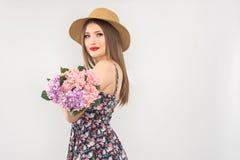 Bionda in un cappello ed in un vestito di paglia con un mazzo dei fiori fotografie stock libere da diritti