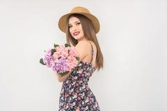 Bionda in un cappello ed in un vestito di paglia con un mazzo dei fiori immagine stock