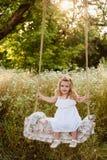 Bionda in un vestito bianco che si siede su un'oscillazione, ridente, infanzia, rilassamento, serenità della bambina Fotografia Stock