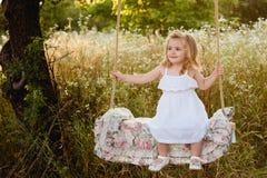 Bionda in un vestito bianco che si siede su un'oscillazione, ridente, infanzia, rilassamento, serenità della bambina Fotografie Stock