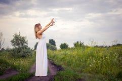 Biondo nel supporto bianco del vestito fra i pini Fotografia Stock