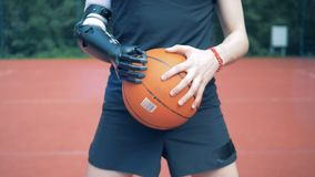 Bionic hand with a ball, close up. Human with a robot arm. Sporting equipment on a basketball court