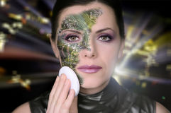 Bionic woman. Removing makeup from her face royalty free stock images