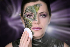 Bionic woman. Removing makeup from her face royalty free stock photos