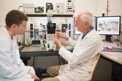 Bioquímico que usa o grandes microscópio e computador com estudante imagens de stock royalty free