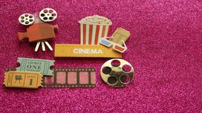 Bioskoopteken met kaartjes van de de glazenfilm van de popcornemmer 3d op filmstrook met een spoel op een donkere roze achtergron royalty-vrije stock foto