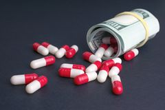 Biotech and pharmaceutical companies. Red white capsules spill out of folded dollars, dark background stock photos
