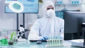 Biotechnologist στην άσπρη φόρμα και μάσκα που λειτουργεί στον υπολογιστή φιλμ μικρού μήκους