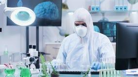 Biotechnologist στη φόρμα που χρησιμοποιεί έναν κυβερνήτη για να μετρήσει το μήκος εγκαταστάσεων απόθεμα βίντεο