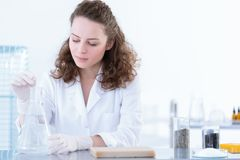 Biotechnologist dissolving sample in solution. Biotechnologist dissolving the sample in a solution during laboratory analysis Stock Images