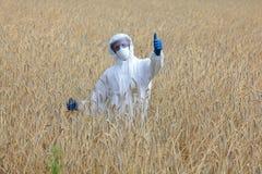 Biotechnologist met duim op gebaar op gebied Stock Foto's