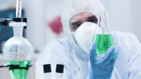 Biotechnologist que olha uma amostra com líquido verde video estoque