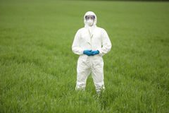 Biotechnology engineer on field of genetically mod. Biotechnology engineer in white uniform, mask, goggles on field of genetically modified crops portrait Stock Photo