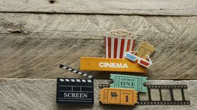 Biotecknet med skärmen för biljetter för filmen för exponeringsglas för popcornhinken 3d den stora öppnade asken på träbakgrund royaltyfri fotografi