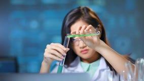 Biotecnologia de condução da análise do químico da mulher que faz o close-up médio da investigação médica filme