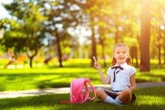 bipeds Меньшая девушка школы с розовым рюкзаком сидя на траве после уроков и думая идей, прочитала книгу и исследование стоковое фото rf