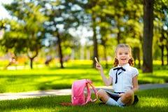 bipeds Меньшая девушка школы с розовым рюкзаком сидя на траве после уроков и думая идей, прочитала книгу и исследование стоковое фото
