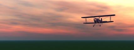 Biplan durch Sonnenuntergang Stockbild